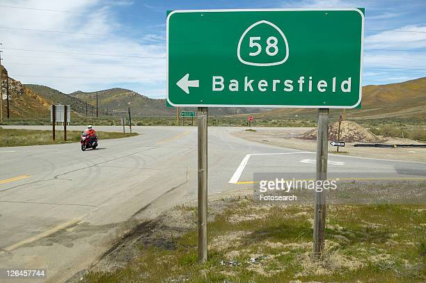 A motorcycle driving past a road sign