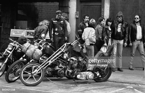 Motorcycle enthusiasts admire customized motorcycles in Daytona Beach Florida during the city's 1983 Bike Week The annual motorcycle event and rally...