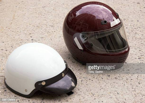 Motorcycle helmets rest on asphalt