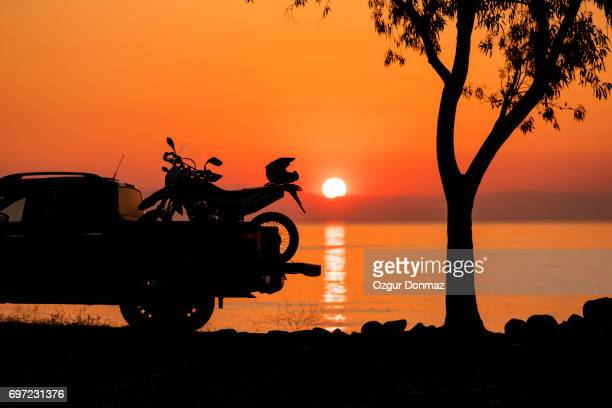 Motorcycle in the back of a pickup truck at sunrise