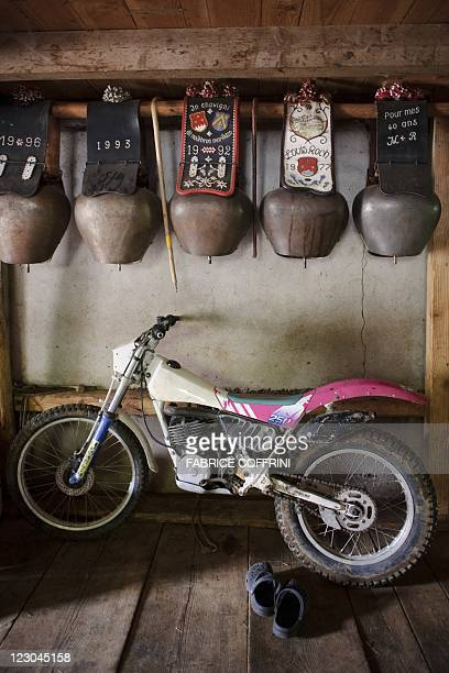 A motorcycle is parked under the cows bells at Jean Louis Roch's Alpine chalet during Gruyere cheese making operations in the mountain pasture of...