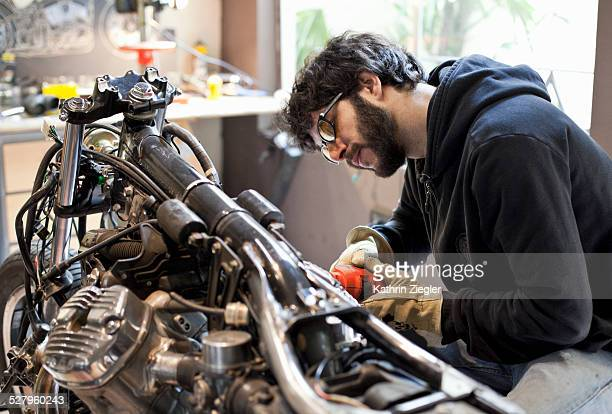 motorcycle mechanic polishing motorbike head