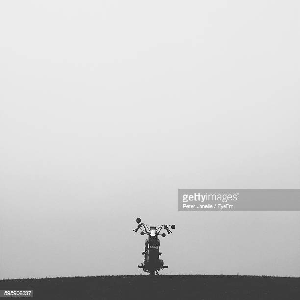Motorcycle Parked On Hill Against Sky
