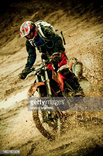 Motorcycle rider in mud riding a motocross race