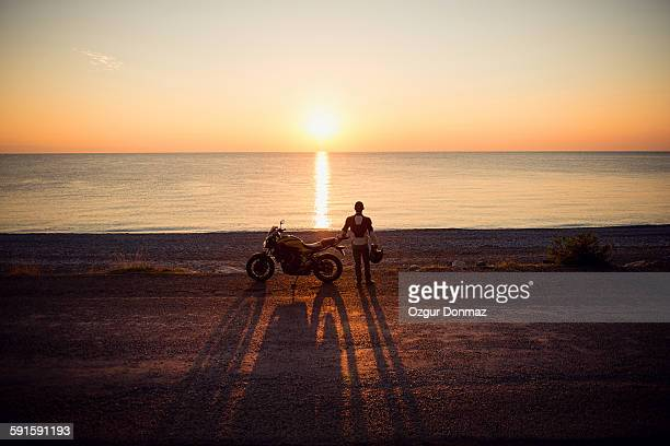 Motorcycle rider on the beach at sunrise