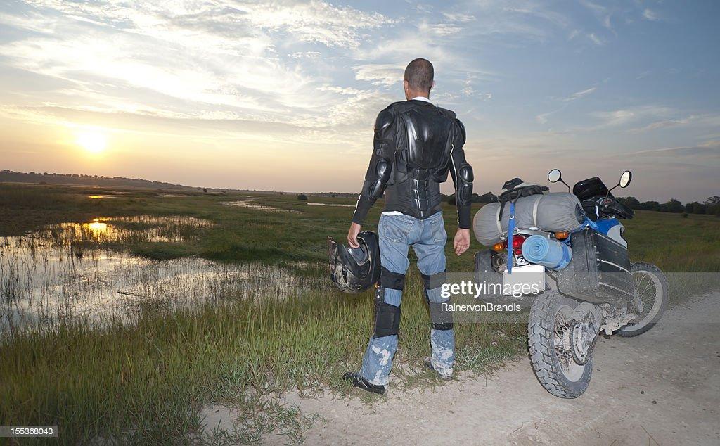motorcycle rider stops to enjoy sunrise