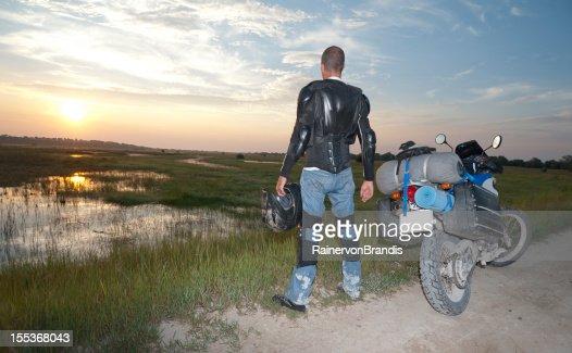 Motorrad Fahrer hält auf den Sonnenaufgang