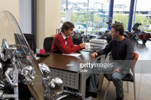 motorcycle salesman pointing to calculator : Stock Photo