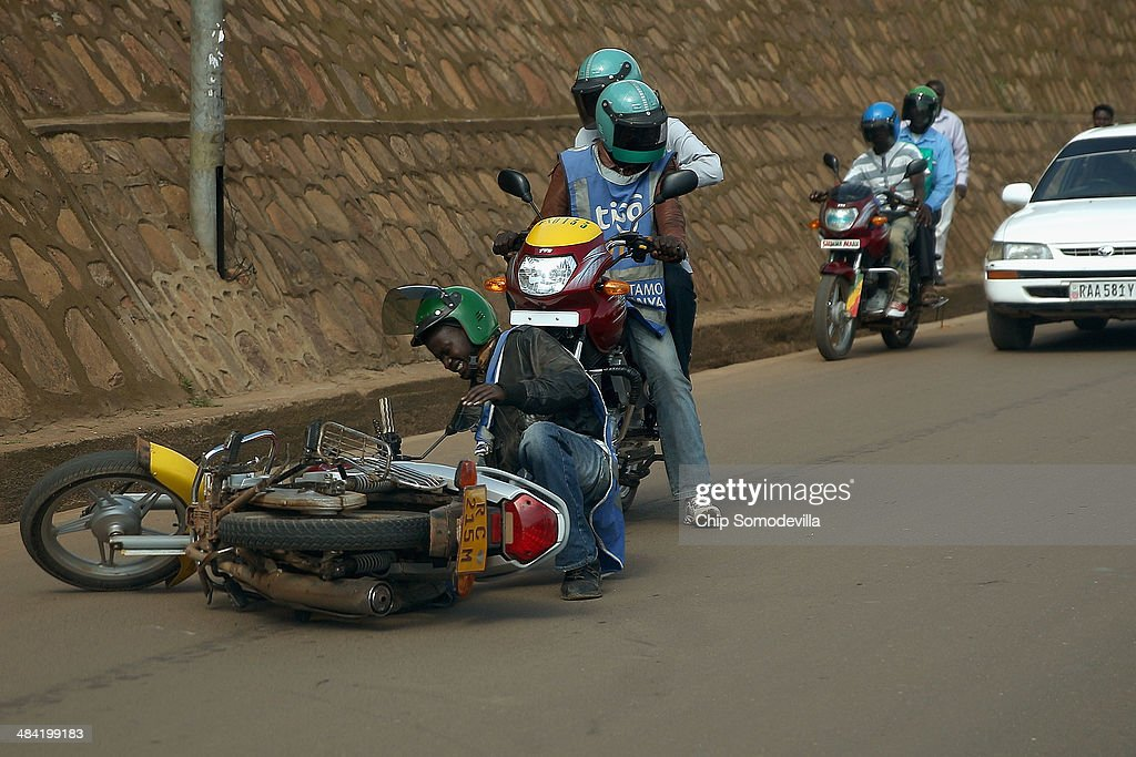 A motorcycle taxi driver gets back on his feet after he fell avoiding a collision near the Nyabugogo neighborhood bus park April 10, 2014 in Kigali, Rwanda. Called 'boda-boda' in East Africa, the motorcycles dominate the roads in Kigali, a city build on a serise of hills and valleys. Many drivers pay dues and belong to co-operatives which represent their interests with local and central government agencies. As motorcycles cost more than 1.3 million Rwandan Francs (or about $1900 US), many riders pay a weekly fee of about $40 US to the bike owners and keep whatever they make beyond that amount. Working 13-hour shifts, boda-boda drivers can carry about 25 passengers on a good day of business.
