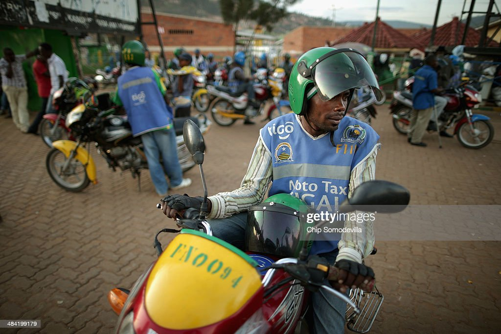 Motorcycle taxi driver Jean Claude Bigirimana, 31, waits for a customer at the Nyabugogo neighborhood bus park April 9, 2014 in Kigali, Rwanda. Called 'boda-boda' in East Africa, the motorcycles dominate the roads in Kigali, a city build on a serise of hills and valleys. Many drivers pay dues and belong to co-operatives which represent their interests with local and central government agencies. As motorcycles cost more than 1.3 million Rwandan Francs (or about $1900 US), many riders pay a weekly fee of about $40 US to the bike owners and keep whatever they make beyond that amount. Working 13-hour shifts, boda-boda drivers can carry about 25 passengers on a good day of business.