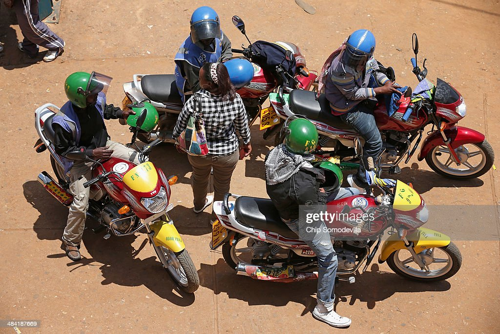 Motorcycle taxi drivers, called 'boda-boda' in East Africa, surround a potential passenger near the Nyabugogo neighborhood bus park April 9, 2014 in Kigali, Rwanda. Boda-boda dominate the roads in Kigali, a city build on a serise of hills and valleys. Many drivers pay dues and belong to co-operatives which represent their interests with local and central government agencies. As motorcycles cost more than 1.3 million Rwandan Francs (or about $1900 US), many riders pay a weekly fee of about $40 US to the bike owners and keep whatever they make beyond that amount. Working 13-hour shifts, boda-boda drivers can carry about 25 passengers on a good day of business.