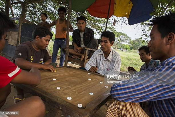 Motorcycle taxi drivers play carrom as they wait for customers in Naypyidaw Myanmar on Wednesday March 9 2016 The country's parliament will reveal...