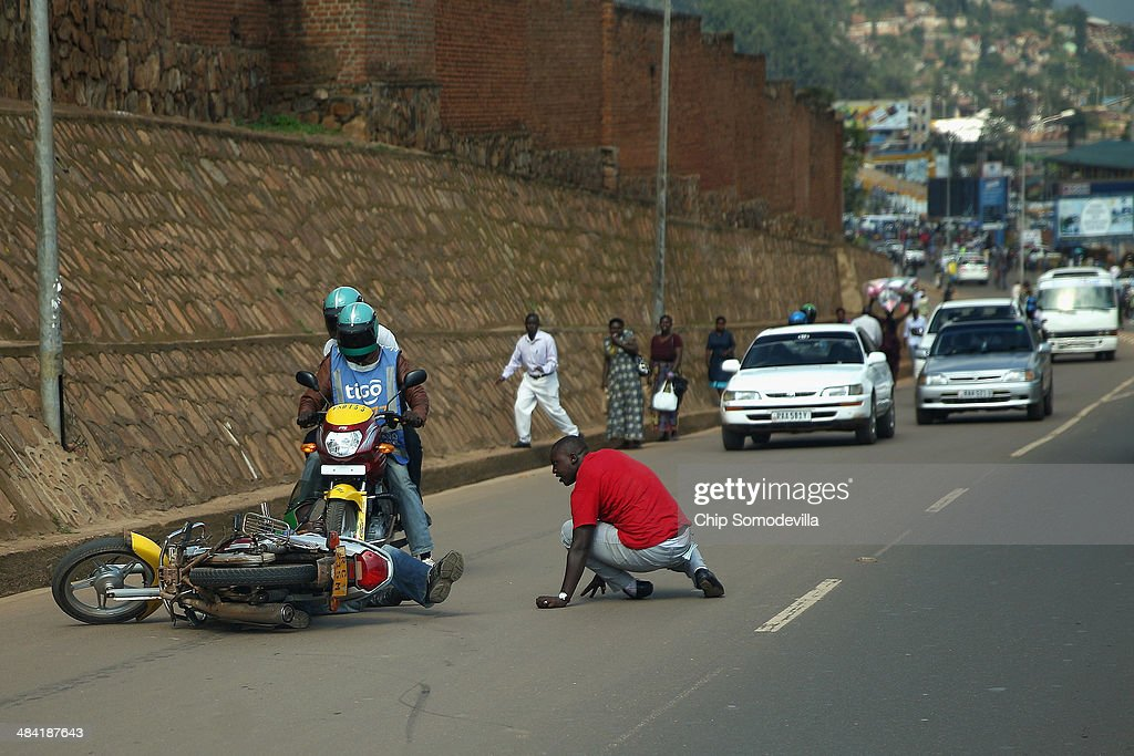 A motorcycle taxi passenger gets back on his feet after his driver crashed the cycle while avoiding a collision near the Nyabugogo neighborhood bus park April 10, 2014 in Kigali, Rwanda. Called 'boda-boda' in East Africa, the motorcycles dominate the roads in Kigali, a city build on a serise of hills and valleys. Many drivers pay dues and belong to co-operatives which represent their interests with local and central government agencies. As motorcycles cost more than 1.3 million Rwandan Francs (or about $1900 US), many riders pay a weekly fee of about $40 US to the bike owners and keep whatever they make beyond that amount. Working 13-hour shifts, boda-boda drivers can carry about 25 passengers on a good day of business.