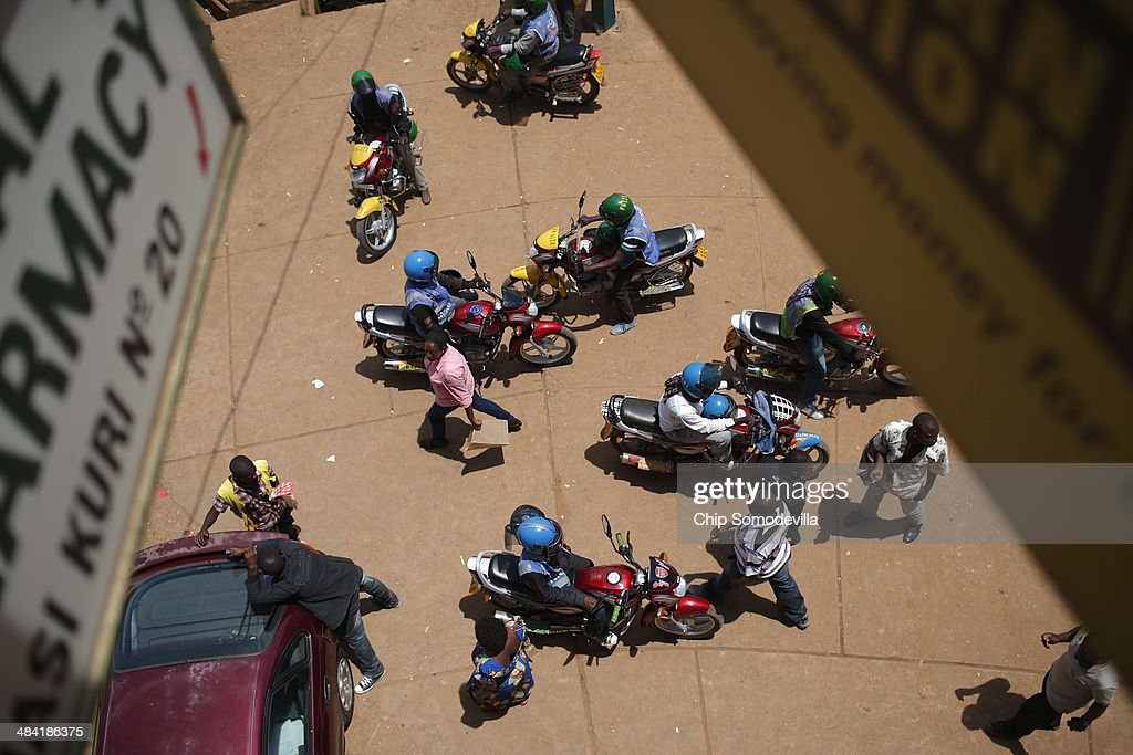 Motorcycle taxis, called 'boda-boda' in East Africa, wait for passengers at the Nyabugogo neighborhood bus park April 9, 2014 in Kigali, Rwanda. Boda-boda dominate the roads in Kigali, a city build on a serise of hills and valleys. Many drivers pay dues and belong to co-operatives which represent their interests with local and central government agencies. As motorcycles cost more than 1.3 million Rwandan Francs (or about $1900 US), many riders pay a weekly fee of about $40 US to the bike owners and keep whatever they make beyond that amount. Working 13-hour shifts, boda-boda drivers can carry about 25 passengers on a good day of business.