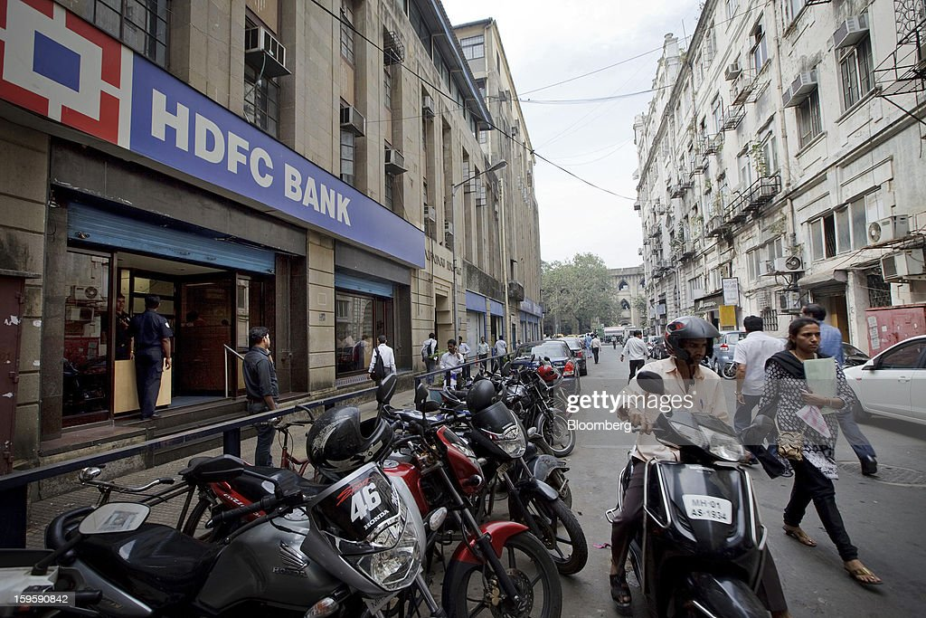 Motorcycles are parked in front of an HDFC Bank Ltd. branch in Mumbai, India, on Wednesday, Jan. 16, 2013. India's financial system has been made vulnerable by a deterioration in bank assets and a lack of capital as the economy slowed, according to the International Monetary Fund. Photographer: Kuni Takahashi/Bloomberg via Getty Images