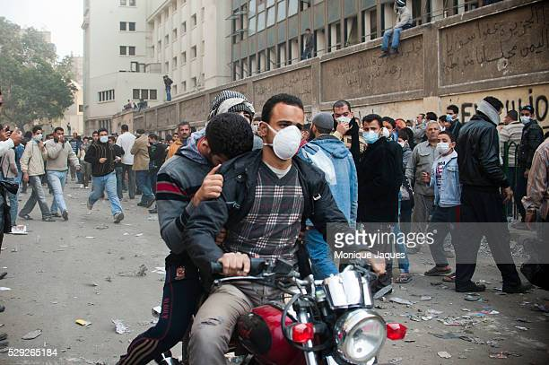 Motorcycles ferry out those suffering from gas inhalation during violent protests between Protestors in Tahrir Square and the Egyptian Police a week...