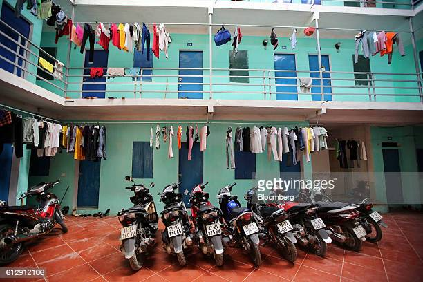 Motorcycles sit parked and clothing hangs from a washing line at a guest house that provides accommodation to workers of the Samsung Electronics...