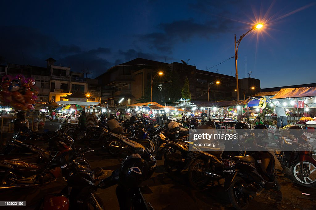 Motorcycles stand parked outside the Pasar Badung market at dusk in Denpasar, Bali, Indonesia, on Tuesday, Oct. 8, 2013. Bank Indonesia said it will regulate currency hedging by individuals and companies, including state-owned firms, to help stabilize Asias most-volatile currency. Photographer: SeongJoon Cho/Bloomberg via Getty Images
