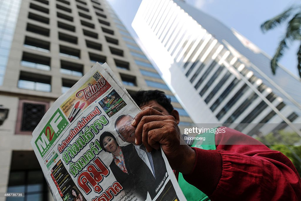 A motorcycle-taxi driver reads a copy of a newspaper featuring ousted Prime Minister Yingluck Shinawatra and interim Prime Minister Niwattumrong Boonsongpaisan on its front page in the Sathorn financial district in Bangkok, Thailand, on Thursday, May 8, 2014. The baht fell to a one-month low and stocks slumped on concern global investors will shun Thailand after a court ruling to remove Yingluck Shinawatra as prime minister worsened the nation's political crisis. Photographer: Dario Pignatelli/Bloomberg via Getty Images