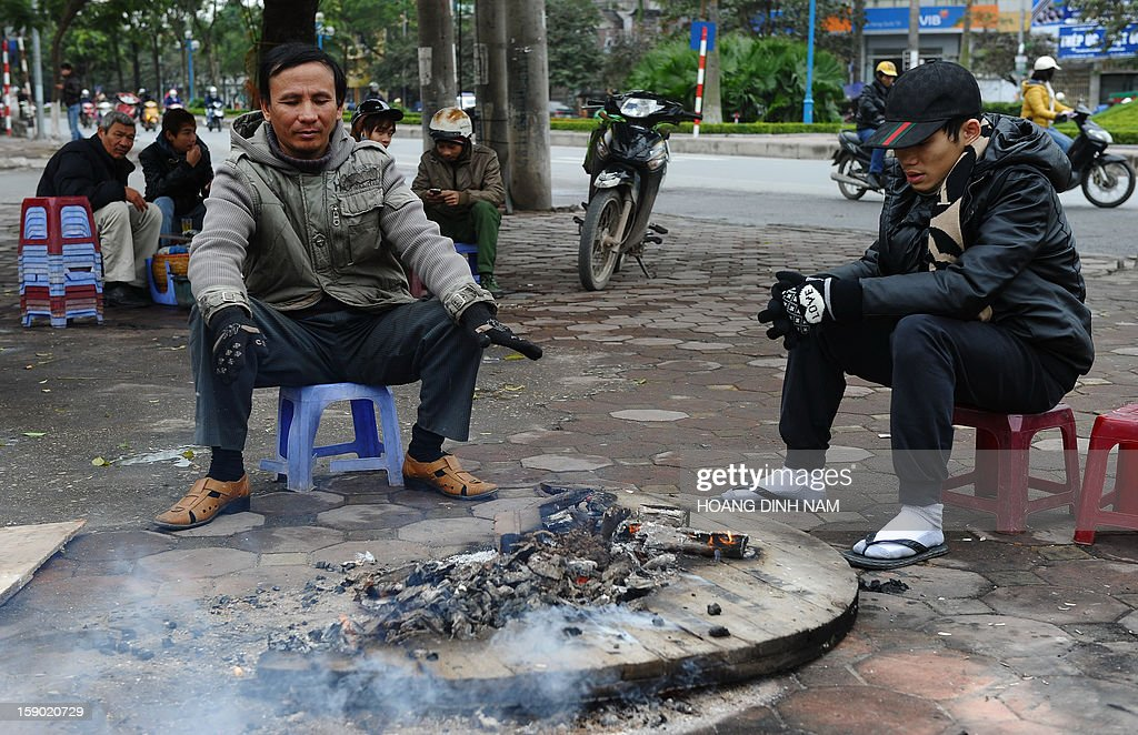 Motorcycle-taxi drivers sit around a fire to keep warm on a street in downtown Hanoi on January 6, 2013 as northern Vietnam faces the toughest cold wave so far this season. Tempetures have dropped below 0 C (32F) in some mountainous areas bordering with China and elementary schools have been closed since January 4. AFP PHOTO / HOANG DINH Nam