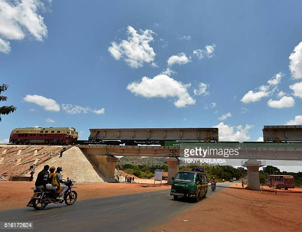 A motorcyclist and a van run down a street as they approach an underpass beneath a section of Standard Gauge Railway in Kenya near Voi at 332 kms...