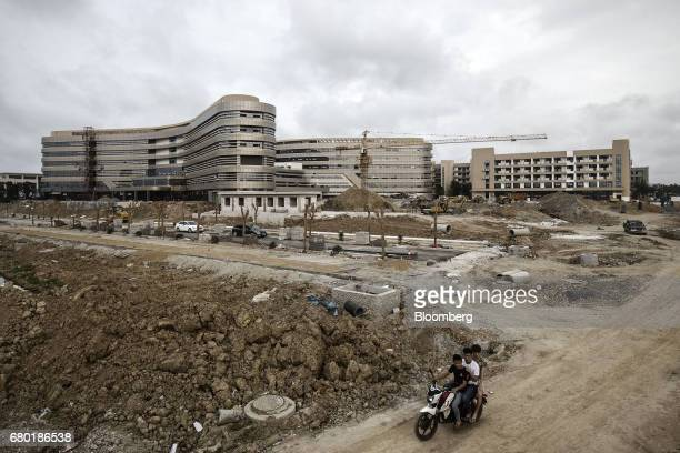 A motorcyclist and his passengers ride past the under construction Evergrande International Hospital inside the Hainan Boao Lecheng...