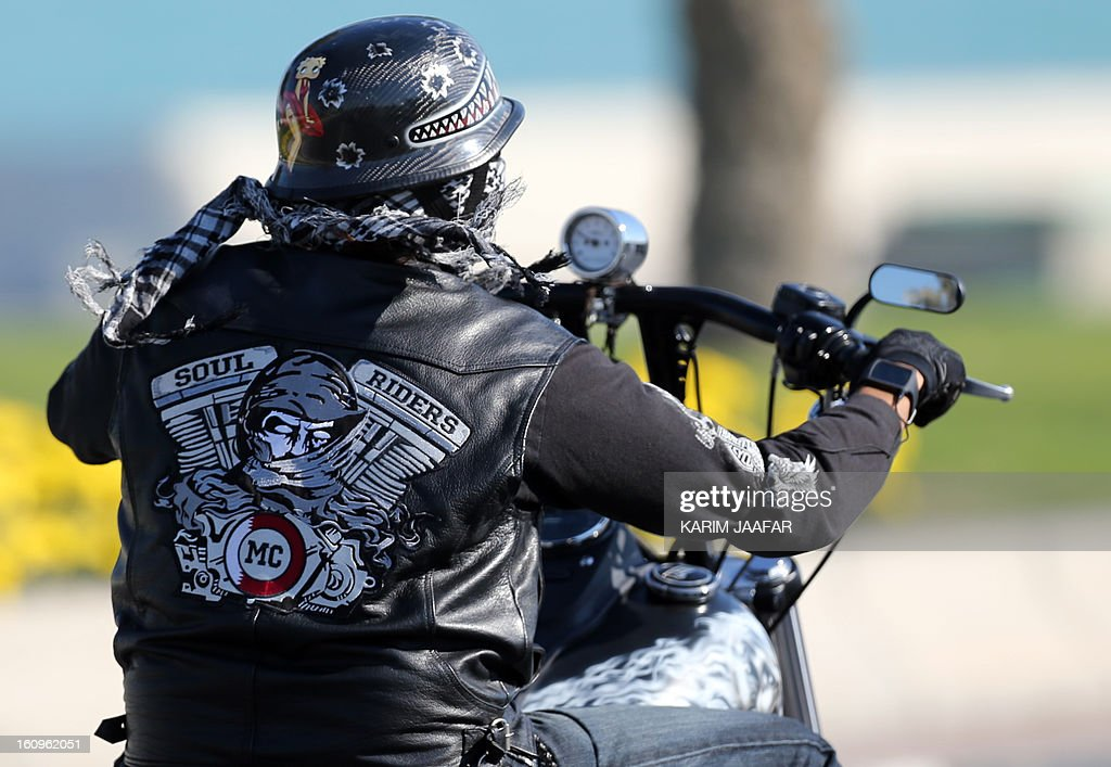 A motorcyclist, belonging to the Soul Riders group, parades on his Harley Davidson during the last stage of the 2013 cycling Tour of Qatar, from Cyline beach to the Doha Cornich, on February 8, 2013. The 2011 world champion, Cavendish won the 116.5-kilometre final stage in a sprint finish ahead of Yauheni Hutarovich of Belarus and Barry Markus of the Netherlands.
