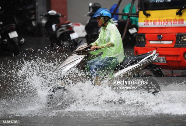 A motorcyclist commutes on a flooded street in Hanoi on July 17 after tropical storm Talas made landfall in northern Vietnam / AFP PHOTO / HOANG DINH...