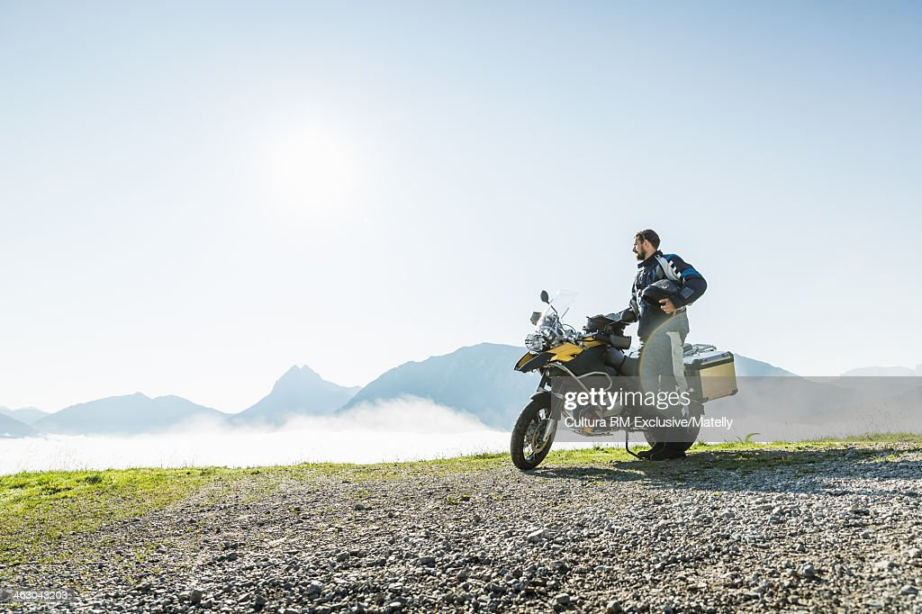 Motorcyclist contemplating view from mountain pass, Tyrol, Austria : Stock Photo