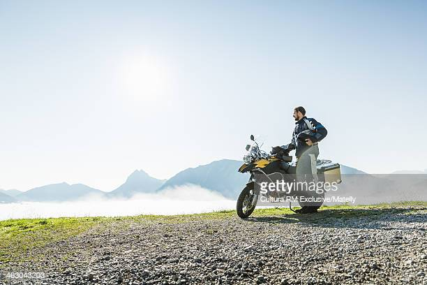 Motorcyclist contemplating view from mountain pass, Tyrol, Austria