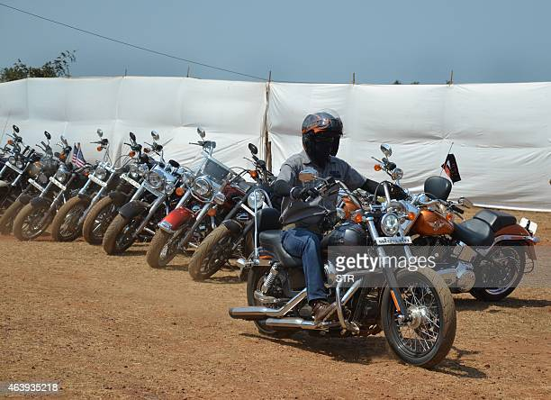 A motorcyclist drives a HarleyDavidson motorcycle past a row of Harleys on display during India Bike Week 2015 at Vagator in southern Goa on February...