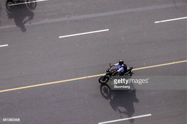 A motorcyclist drives along the Kamarajar Salai road running parallel to Marina Beach in Chennai India on Wednesday July 15 2015 A banking system...