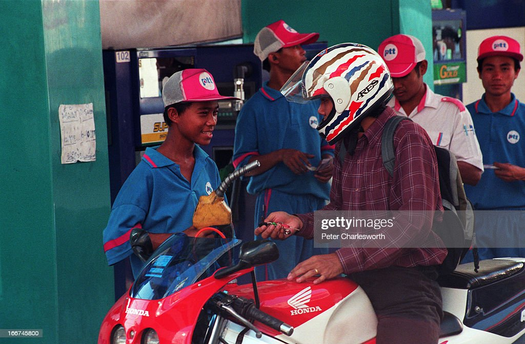 A motorcyclist fills up with petrol with the help of a gas station attendant in the forecourt of a Petroleum Authority of Thailand petrol station