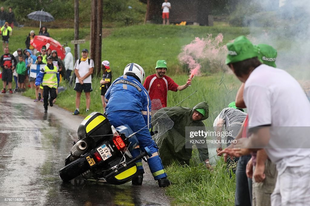A motorcyclist gendarme straighten up his motorcycle after falling during the 1465 km twentieth stage of the 103rd edition of the Tour de France...