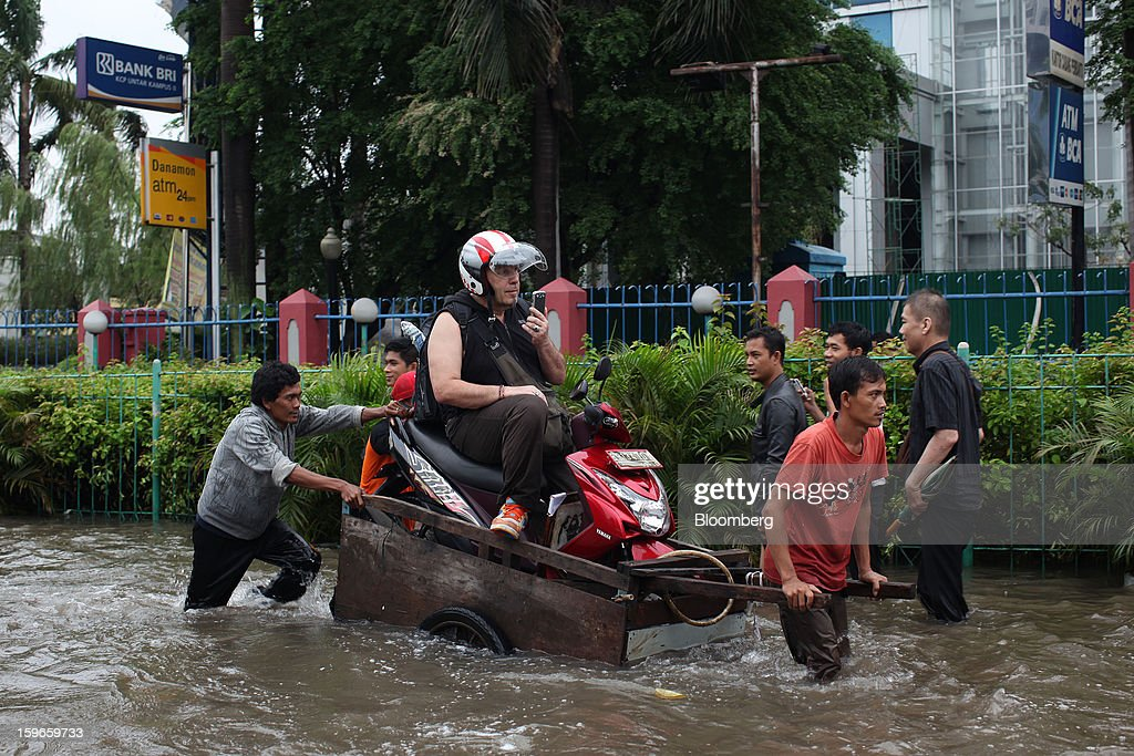 A motorcyclist is ferried through floodwaters on a makeshift cart in Jakarta, Indonesia, on Friday, Jan. 18, 2013. Indonesia declared a state of emergency in Jakarta as flooding brought traffic to a standstill in the city of 9.6 million people and swamped the offices of President Susilo Bambang Yudhoyono. Photograph by: Dimas Ardian/Bloomberg via Getty Images