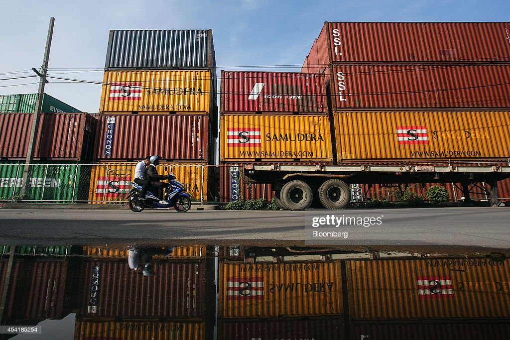 A motorcyclist is reflected in a puddle as he rides past stacked containers at the Custom Global Service Co. container depot in Bangkok, Thailand, on Monday, Aug. 25, 2014. Thailand's trade figures are scheduled for release on Aug. 27. Photographer: Dario Pignatelli/Bloomberg via Getty Images
