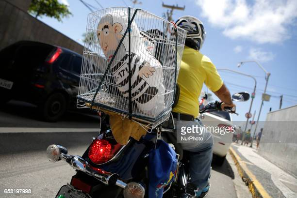 A motorcyclist is seen with a puppet of former president Lula inside a cage on his motorcycle in Recife northeastern Brazil on March 26 2017...