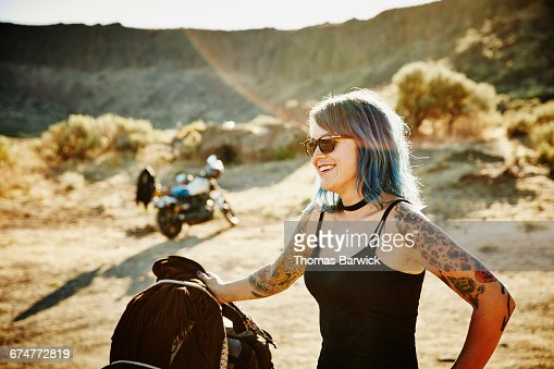 Motorcyclist on road trip standing next to bike