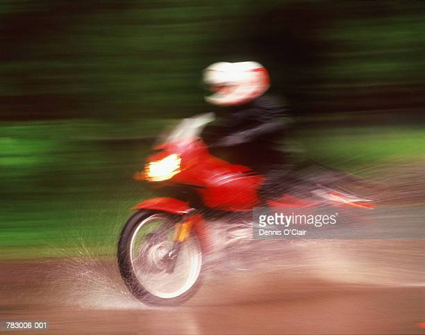 Motorcyclist on wet road (blurred motion)