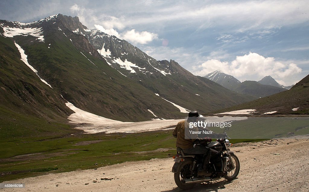 A motorcyclist passes along Srinagar-Leh highway near a treacherous pass on August 22, 2014 in Zojila, about 108 km (67 miles) east of Zojila, has an impressive location, enclosed by Kashmir valley on one side and Drass valley on the other side and functions as a major link between Ladakh and Kashmir, is considered to be the World's most dangerous pass is located at 3529 meters. The average snow buildup on the rocky Zojila- which is part of the 443 km (275 miles) long Srinagar-Leh highway- normally stays in the level of 15 to 25 meters and is closed for half year. It opens up in late spring and witnesses violent breezes because of the conical shape. Travellers on the pass have to face and withstand snowstorms, fierce air currents, cold and highly dangerous circumstances.