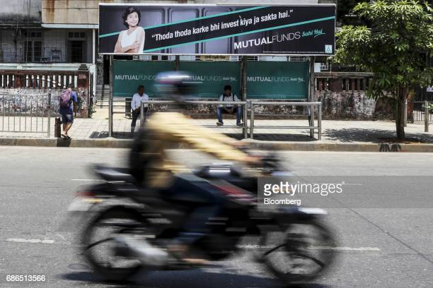 A motorcyclist passes passengers sitting next to an advertisement for the Mutual Funds Sahi Hai campaign by the Association of Mutual Funds in India...