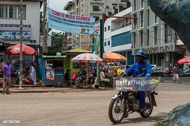 A motorcyclist passes street traders sitting beneath parasols on a road side in Conakry Guinea on Saturday Sept 5 2015 While Guinea produces bauxite...