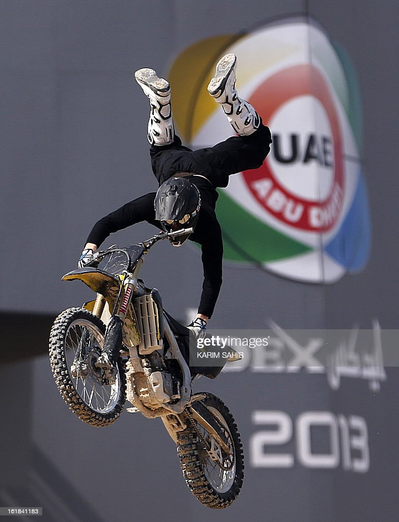 A motorcyclist performs stunts during the opening of the International Defence Exhibition and Conference (IDEX) at the Abu Dhabi National Exhibition Centre in the Emirati capital on February 17, 2013.