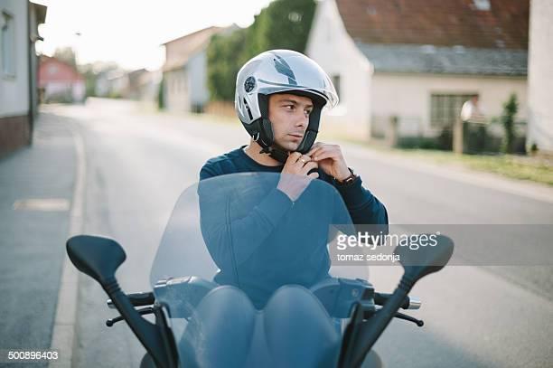 Motorcyclist putting on a helmet