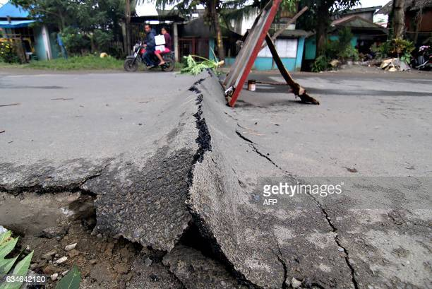 A motorcyclist rides around an asphalt road which was damaged after a 65magnitude earthquake struck overnight in Surigao City in southern island of...