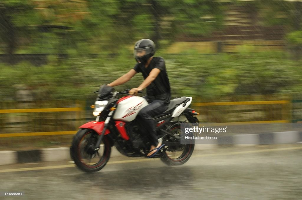 A motorcyclist rides during a heavy rainfall after a hot and humid afternoon on June 29, 2013 in Noida, India. Weather department forecast the country will receive normal rains this year, raising prospects of a stronger performance by Asia's third-largest economy.