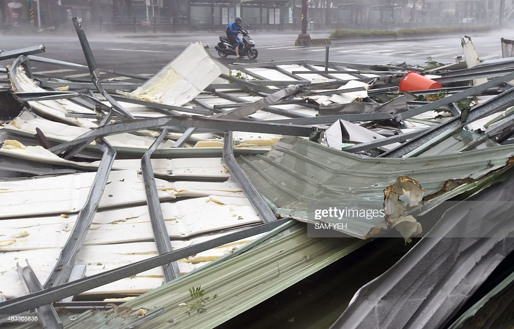 A motorcyclist rides past a damaged roof as typhoon Soudelor hits Taipei on August 8 2015 Typhoon Soudelor battered Taiwan with fierce winds and rain...