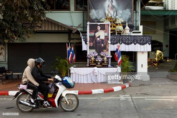A motorcyclist rides past a portrait of Thailand's Crown Princess Maha Chakri Sirindhorn and her father the late King Bhumibol Adulyadej in Nan Nan...