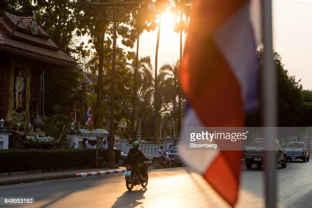 A motorcyclist rides past a portrait of Thailand's King Maha Vajiralongkorn and a Thai national flag in Nan Nan Province Thailand on Friday March 3...