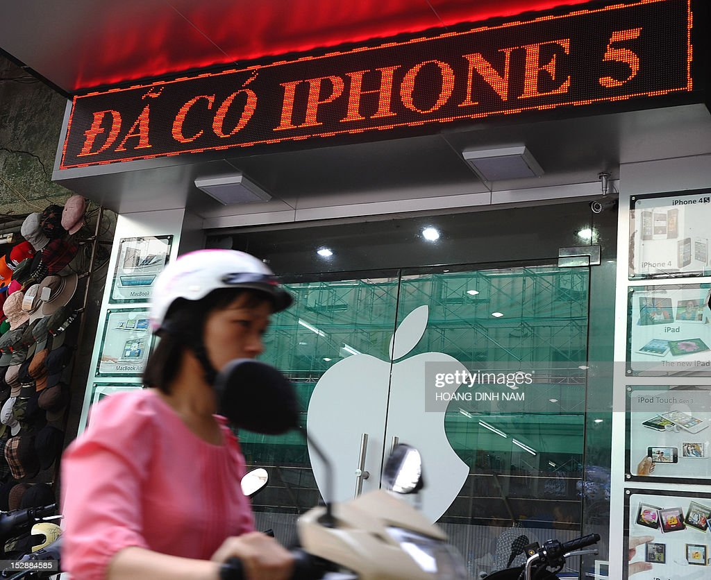 A motorcyclist rides past a shop selling Apple products with a digital advertising display announcing that Apple's smart phone Iphone 5 is available for sale on a street in downtown Hanoi on September 28, 2012. Not being among themarkets choosen for Apple's inaugural sale of the Iphone 5, Vietnam's smart phone market gets feverish with hi-tech lovers and wealthy people ready to pay up to 23 million dongs or 1,100 USD for an Iphone 5 16G model, all of which are imported by individuals from Singapore, Hongkong or the US. AFP PHOTO/HOANG DINH Nam